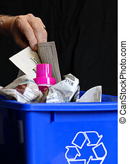 hand putting recycling in bin with plastic and paper