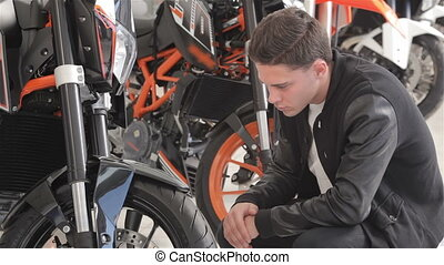 Close up of a young client examines motorbike - Smiling...