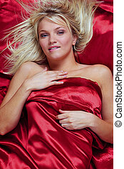 Blond woman biting her lip in bed