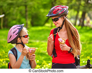 Bikes cycling girls with rucksack cycling eating ice cream...