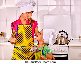 Children cooking at kitchen. - Children wearing hat and...