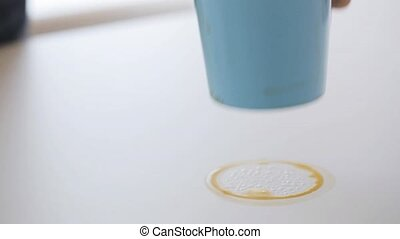 woman with rag cleaning coffee stain on table - people,...