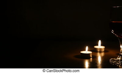 Wine glasses and burning candles. - Two glasses of wine on...