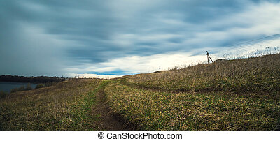 road in field on the background of dark sky before rain -...