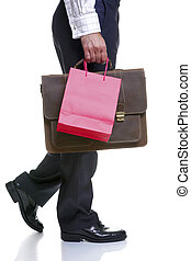 Legs of a man carrying gift bag and briefcase
