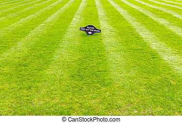 Perfectly striped freshly mowed garden lawn with a warning sign