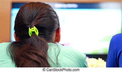 Girls with remote watching TV - Relaxed teenage girls with...
