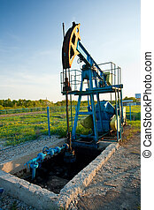 Oil pump at sunset - Industrial landscape with an oil pump...