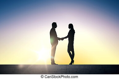 business partners silhouettes shaking hands - business,...