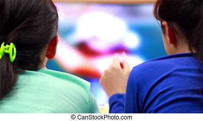 Girls watching tennis sport on TV - Two happy teenage girls...