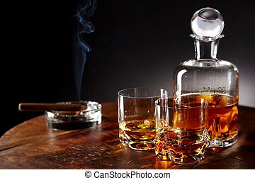 Decanter of alcohol by smoking cigar on a table - Decanter...