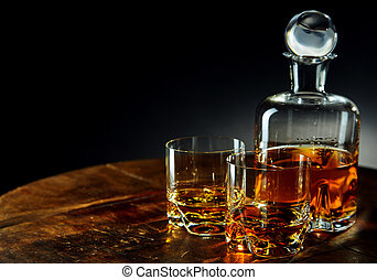 Decanter of whiskey besides two glasses half filled
