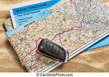 Car remote key on map and rental agreement on sand
