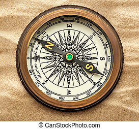 Vintage brass compass on sand in closeup
