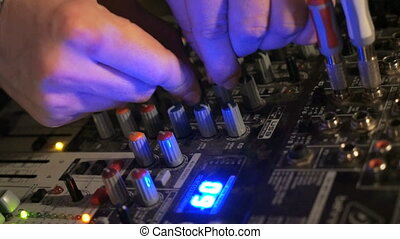 DJ works on the mixer console in night club