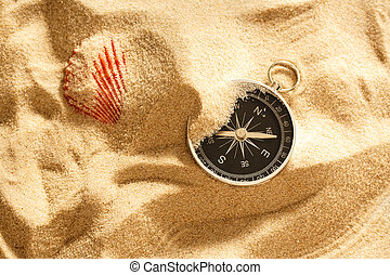 Black compass and sea shell in sand closeup