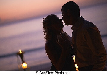 Beautiful young couple kissing on twilight, standing near...