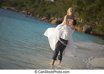 Beautiful young couple enjoying sunset, walking barefoot on...