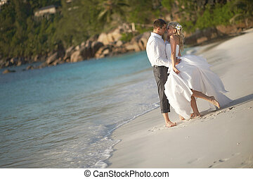 Beautiful young couple kissing on sunset, standing barefoot...