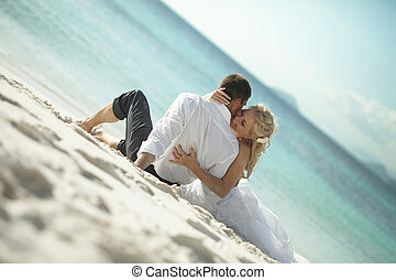 Beautiful young couple kissing on sunset lying on sand,...