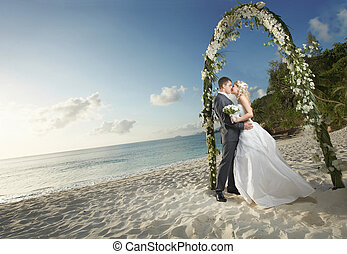 Gorgerous couple kissing, standing under wedding arch during...