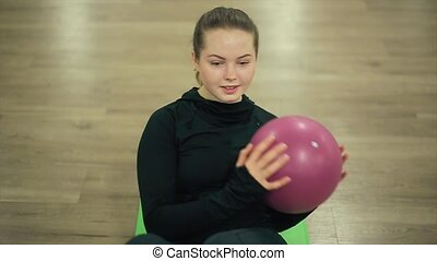 Sport Girl Shakes Press with Ball in Gym