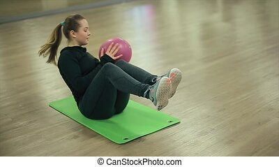 Sport Girl Shakes Press with Ball in Gym.