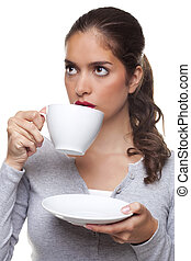 Woman drinking tea from a cup and saucer