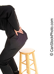 Businessman with back pain - A business man getting up from...