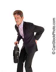 Businessman walking with back pain - A young business man...