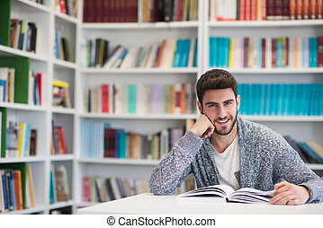 portrait of student while reading book in school library -...