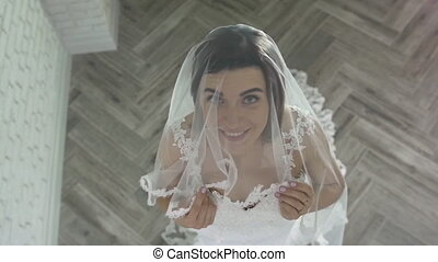 Bride Top View. Beautiful Charming bride in a luxurious dress looking up. beautiful girl in a white dress, blur, view through the chandelier