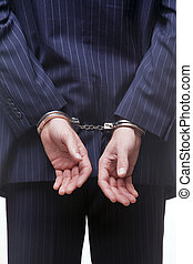 Businessman in handcuffs - Rear view of a businessman in...