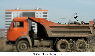 Orange excavator loads the clay into dump truck - Orange...