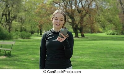 Young Girl Using Smartphone Outside at Green Trees
