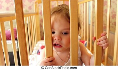 the child plays in a cot - the child fun plays in a cot