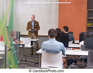 senior teacher and students group in computer lab classroom...