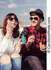 Blowing soap bubbles - Young hipster couple blowing soap...