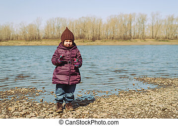 Little girl standing on a riverbank