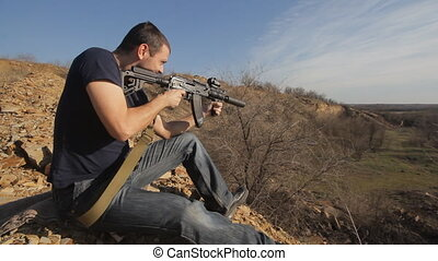 man firing customised russian machine gun, wide - Casually...