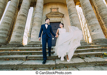 Romantic married couple bride and groom walking down stairs...