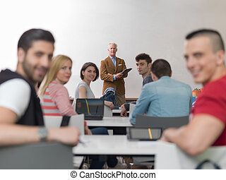 teacher with a group of students in classroom - group of...
