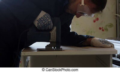 male worker using the jigsaw. Furniture assembly.