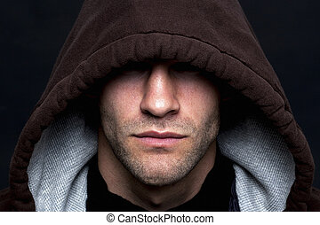 Evil looking hooded man - An evil looking man wearing a...