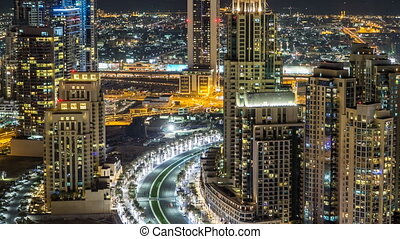 Top view of road in Dubai downtown timelapse with night traffic and illuminated skyscrapers.