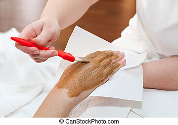 Therapist applying nourishing mask on womans hand
