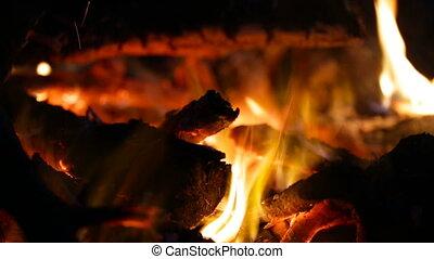 Camera removes coals as fire burns. - Camera removes coals...