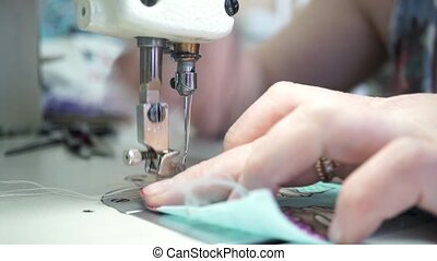 Factory seamstress at work and industrial sewing machine