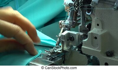 Factory seamstress at work and industrial sewing machine...