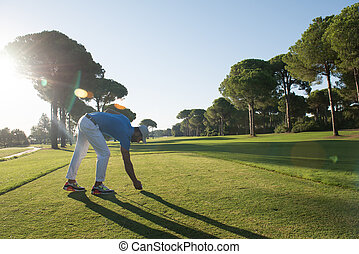 golf player placing ball on tee. beautiful sunrise on golf...